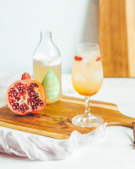 Kombucha Bylinky Zázvor nalitá ve sklenici granátové jablko perlivý probiotický nápoj